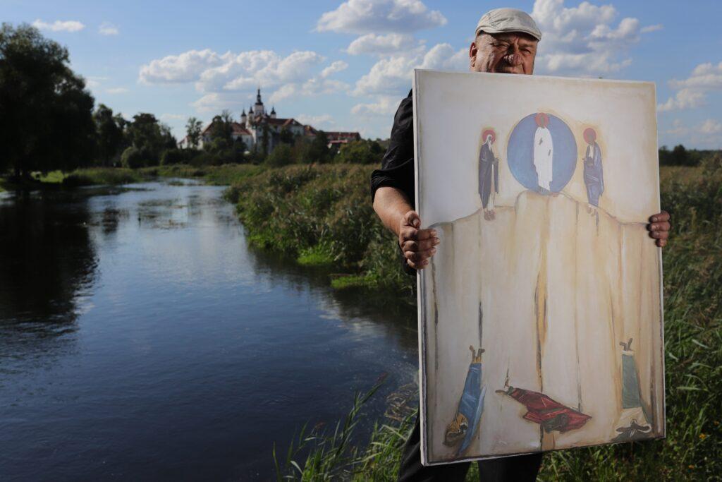 Na pierwszym planie mężczyzna trzymający obraz. W tle rzeka Supraślanka, w oddali zielone drzewa i monaster w Supraślu.