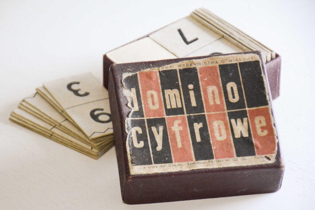 Otwarte kartonowe, bordowe pudełko z napisem na wieku: Domino cyfrowe. Na jasnym tle kartoniki do gry z cyframi.