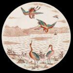 Talerz płaski, okrągły. Na całości jasnobrązowy widok brzegu jeziora z widocznymi w oddali górami i żaglówką na jeziorze. Na pierwszym planie cztery pomarańczowo-zielone żurawie. Dwa stojące na brzegu i dwa w locie.