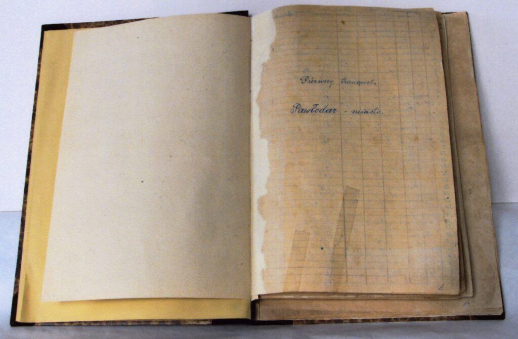 Na zdjęciu jest otwarta, podniszczona księga z odręcznym napisem na pierwszej stronie - Pierwszy transport. Pawłodar miasto.