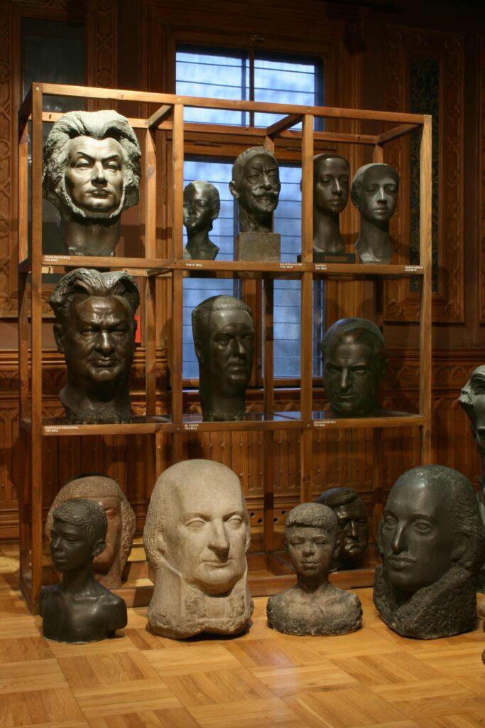 Na zdjęciu widać drewnianą gablotę na której stoją rzeźby głów autorstwa Alfonsa Karnego przedstawiające wybitnych Polaków, m.in. Adama Mickiewicza.