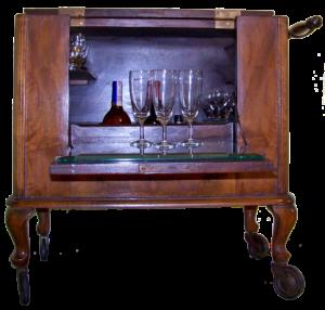 Drewniany mebel barek na czterech nóżkach na kółkach. Ma kształt prostopadłościanu, z odkładanym poziomo od frontu blatem dekorowanym ażurową plecionką promienistą. Blat górny jest dwudzielny, część przednia posiada zawiasy co pozwala otwierać barek od góry, z boku pod blatem znajduje się drewniany uchwyt. Wewnątrz są półki.