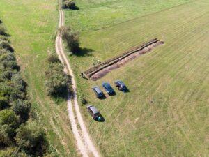 Widok z lotu ptaka na wykopaliska archeologiczne. Na zielonej polanie stoją 4 samochody oraz kopią w ziemi archeolodzy.