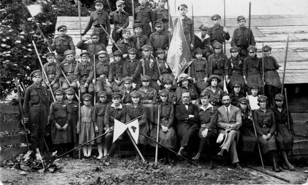 Czarno białe zdjęcie z grupą harcerzy w mundurkach. Dzieci ustawione są do zdjęcia w pięciu rzędach. W rękach trzymają proporczyki i długie kije. Na drugim planie widać drewniany budynek.