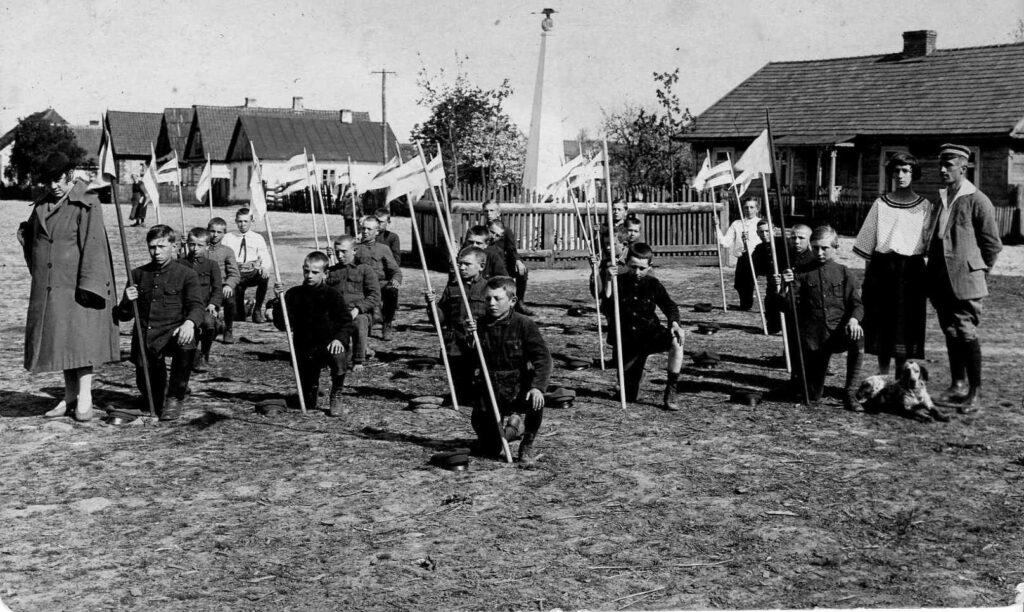 Czarno białe zdjęcie z grupą chłopców w mundurkach, klęczących na prawym kolanie. Każdy z chłopców trzyma w ręku proporczyk. Po bokach stoją dorośli. Na drugim planie widoczne zabudowania oraz Pomnik Orła Białego w Tykocinie.