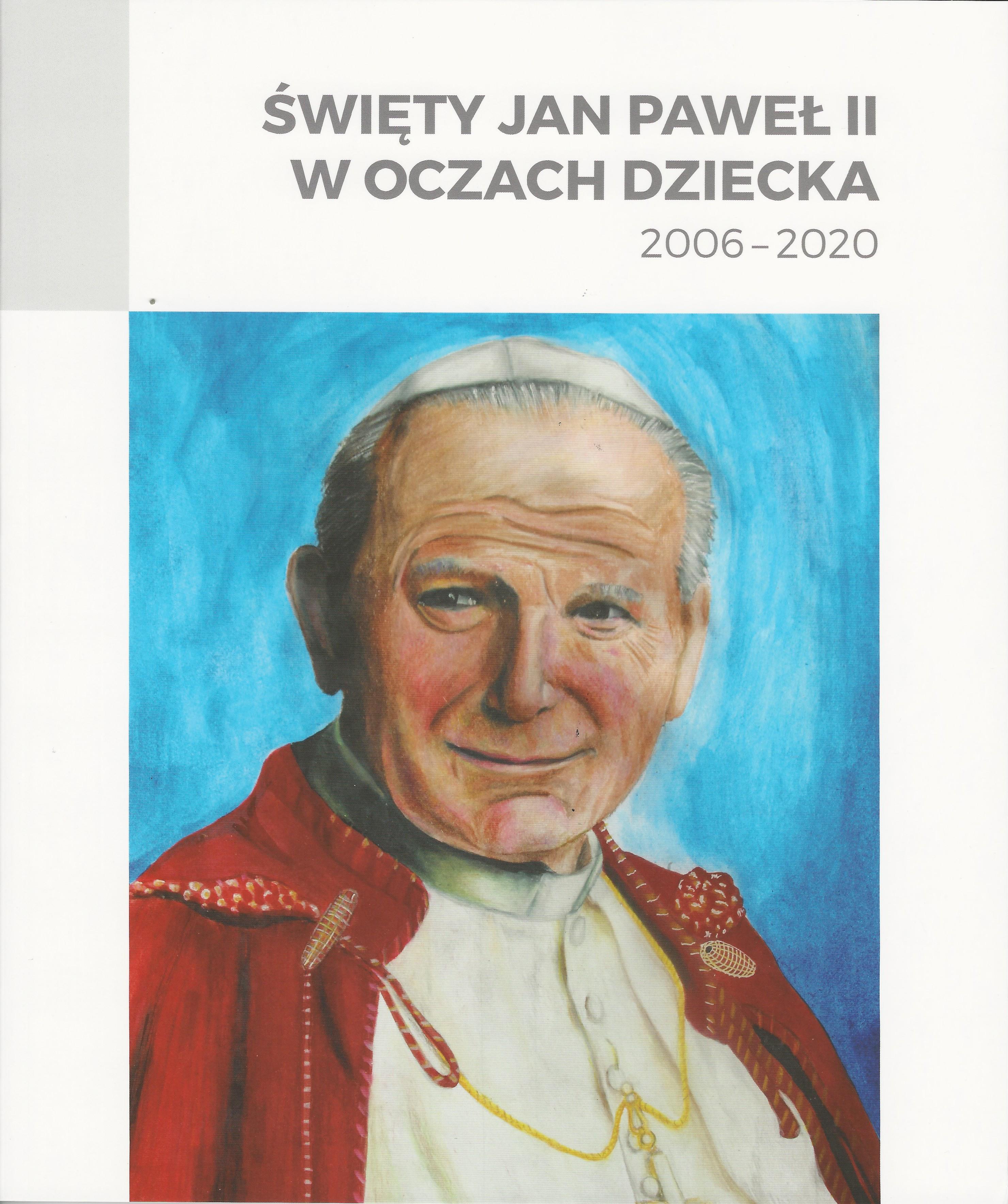 Postać Jana Pawła II w białej sutannie, na ramiona zarzucona czerwona peleryna, na głowie biała piuska. Uśmiecha się.