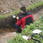 Geomorfolog w trakcie pobierania prób z profilu jednego z wykopów otworzonych na osadzie