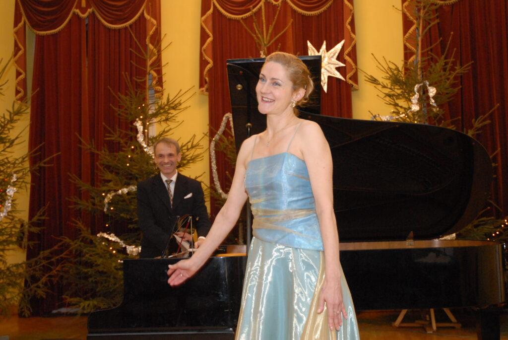 Na pierwszym planie młoda kobieta w błękitnej długiej sukni, śpiewa. W oddali mężczyzna ubrany na czarno, w średnim wieku, gra na fortepianie. W tle zielona choinka.