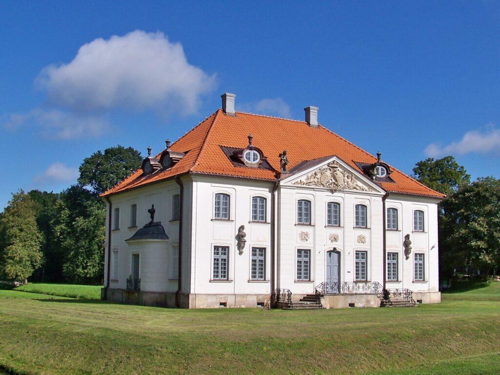 Pałacyk w Choroszczy. W tle niebieskie niebo i zielone drzewa.