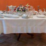 Stół nakryty białym obrusem, zastawiony zastawą.