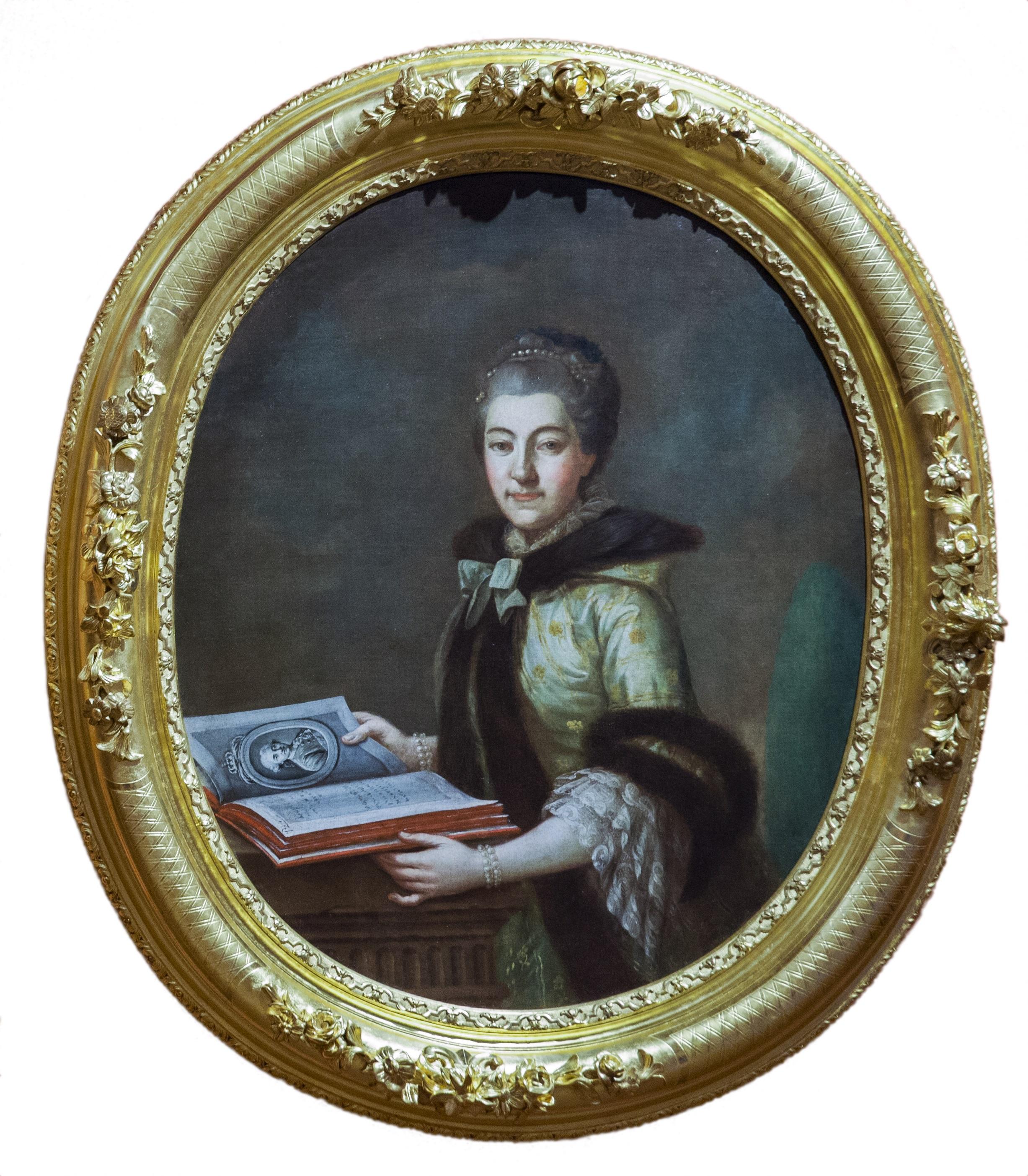 Na owalnym obrazie w pozłacanej ramie widać kobietę w średnim wieku, Izabelę Branicką. Trzyma otwartą książkę.
