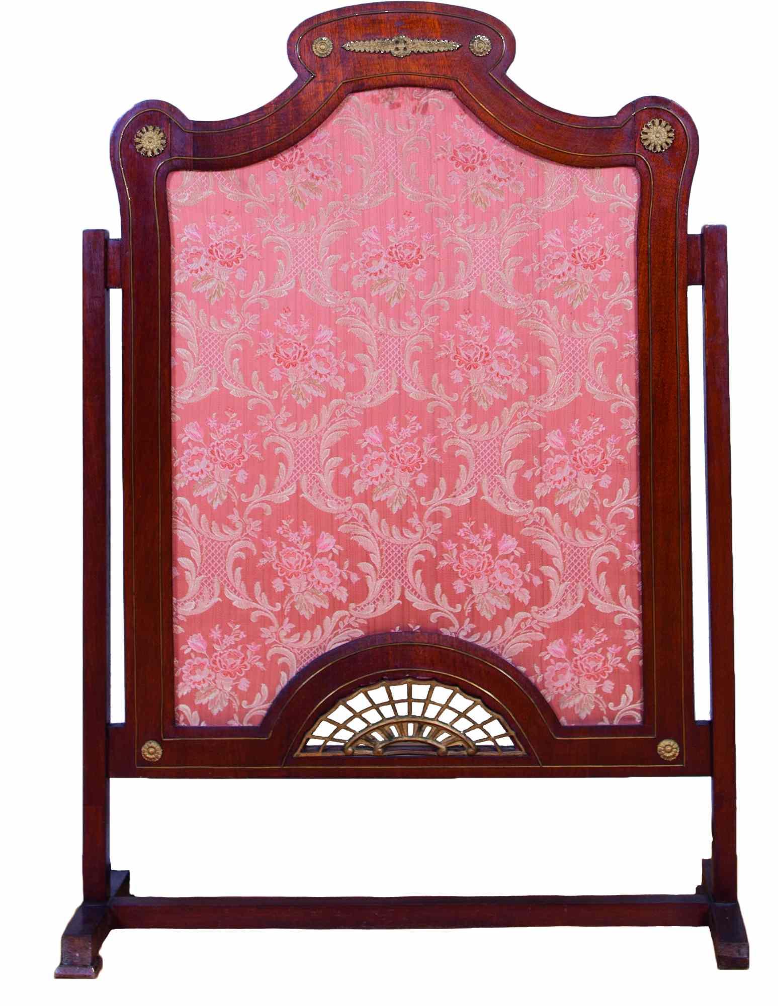 Ekran kominkowy, eklektyczny z drewnianymi, brzozowo – mahoniowymi nóżkami. W środku różowa, wzorzysta tkanina jedwabna.