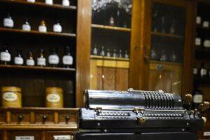 Widać maszynę do pisania na tle kredensu aptecznego